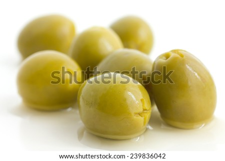 Pitted green olives with brine on white. - stock photo
