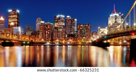 Pittsburgh Skyline at Night:  A view of Pittsburgh, Pennsylvania's cityscape at night overlooking the Allegheny River with views of the Roberto Clemente Bridge and Andy Warhol Bridge. - stock photo