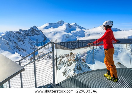 PITZTAL SKI RESORT, AUSTRIA - MAR 29, 2014: Woman skier standing on platform looking at Wildspitze mountain, second highest peak in Austria. March is most sunny month for ski holidays. - stock photo