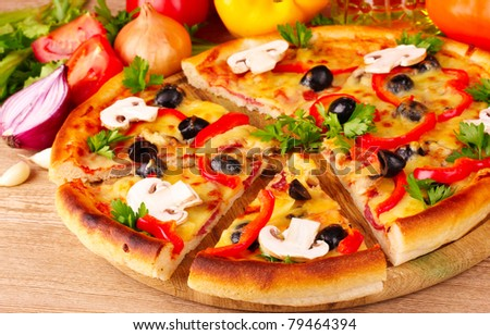 pizza and vegetables on wooden background - stock photo