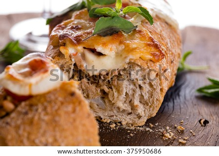 pizza baguette with mozzarella onion and tuna decorated with basil leafs - stock photo