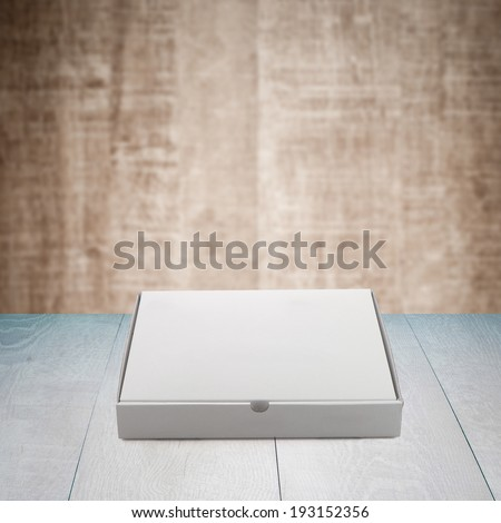 Pizza box paperboard on wooden table. - stock photo