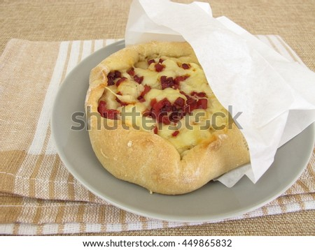 Pizza bread street food with cheese and ham in greaseproof paper bag