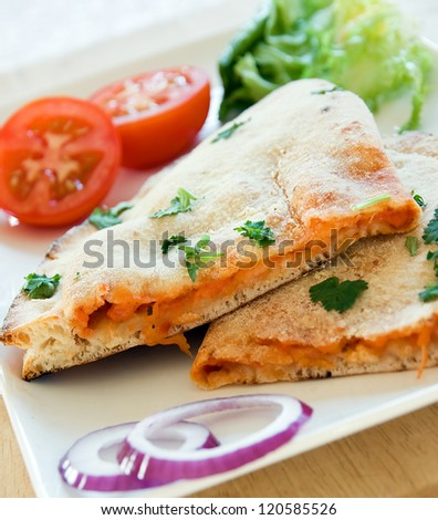 Pizza Calzone on a white plate with a salad accompaniment - stock photo