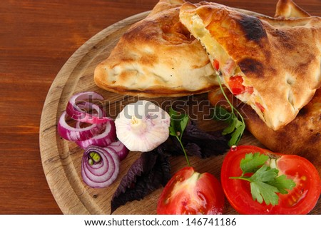 Pizza calzones on wooden board on wooden table