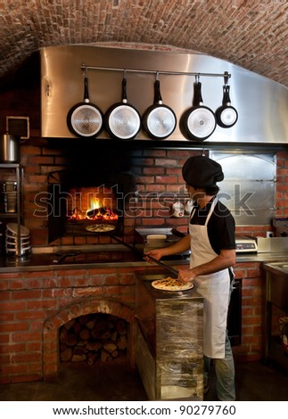 Pizza Chef puts the pizza inside the Wood Oven to bake - stock photo