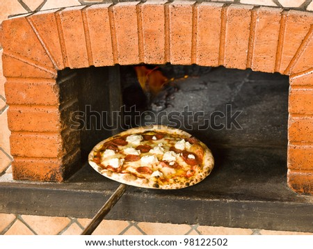 Pizza coming out of a wood burning pizza oven - stock photo
