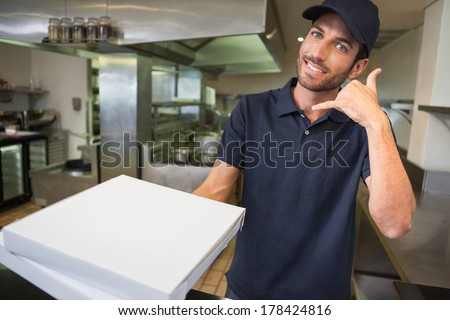 Pizza delivery man holding pizza boxes making a phone gesture in a commercial kitchen - stock photo