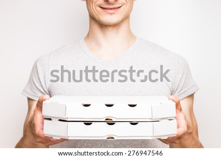 Pizza delivery man in grey t-shirt holds two boxes with food.  - stock photo
