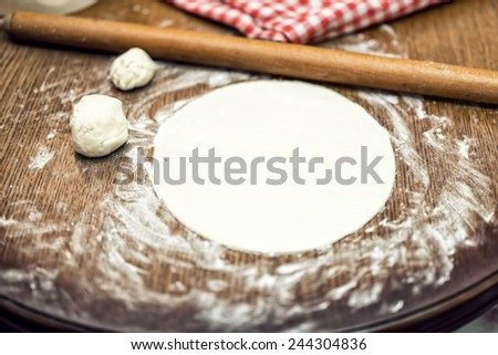 Pizza dough with rolling-pin and flour, on wooden table - stock photo