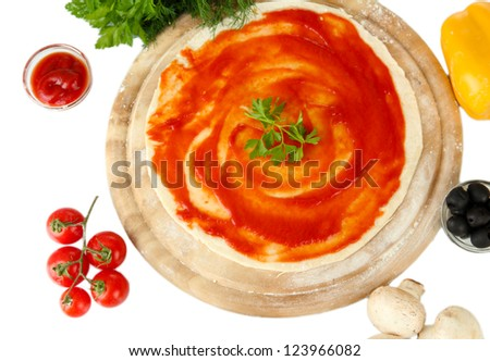 Pizza dough with tomato sauce on wooden board isolated on white - stock photo
