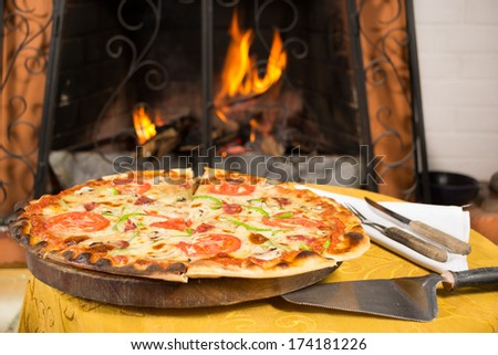 Pizza entering a wood oven - stock photo