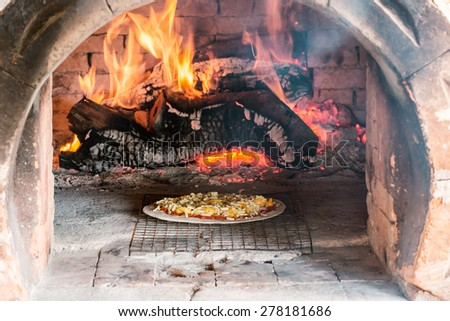 Pizza hawaii cooking in traditional wood fire oven - stock photo