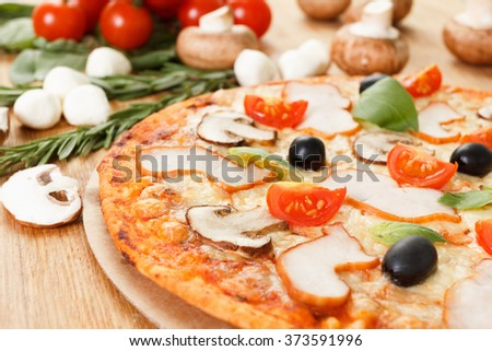 Pizza homemade with mushrooms, olives and tomato. Basil, rosemary and fresh vegetables.