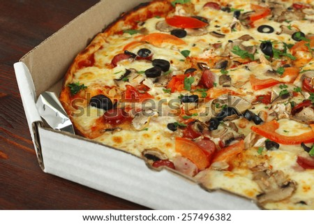 pizza in a box on a wooden background - stock photo