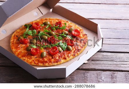 Pizza in box on wooden table, closeup - stock photo