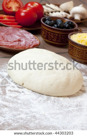 Pizza ingredients on a kitchen table - stock photo