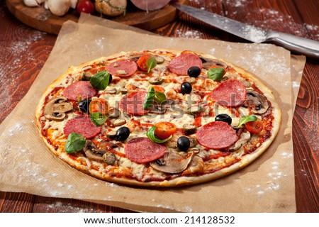Pizza made with Salami, Mozzarella, Mushrooms, Olives and Tomato Sauce - stock photo