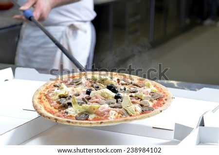 Pizza Man chef serves freshly baked pizza on a carton box for take away - stock photo
