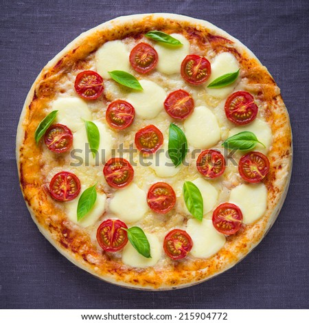 Pizza Margherita on dark canvas background top view - stock photo