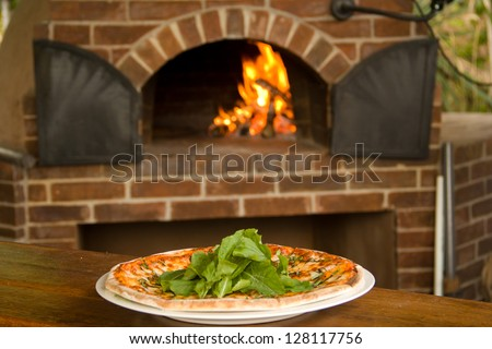 Pizza on a plate with pizza oven in background - stock photo