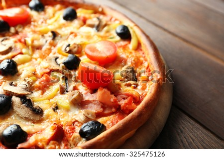 Pizza on cutting board on wooden background