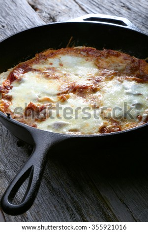 Pizza out of the oven cooked in a cast iron skillet at home - stock photo
