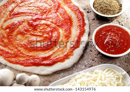 pizza preparation surrounded by ingredients - stock photo
