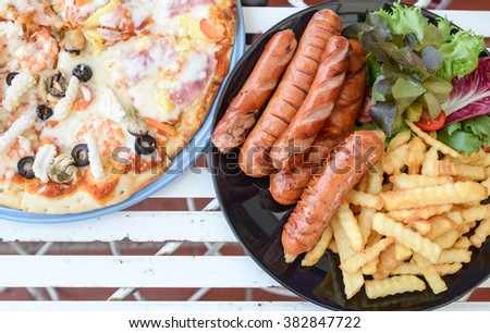 Pizza,sausage,French fries,Vegetables on iron table. - stock photo