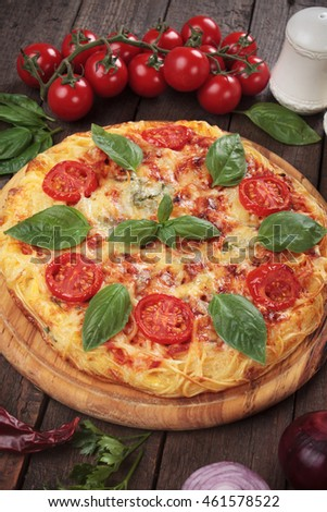 Pizza shaped omelet with spaghetti pasta, cheese and cherry tomato