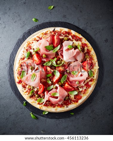 Pizza topped with black forest ham, capers and tomatoes - stock photo