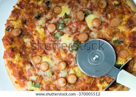 Pizza topped with sausage, vegetables and cheese with a Pizza Cutter / Pizza