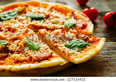 pizza with bacon, mozzarella and spinach in a dark woody background. tinting. selective focus on spinach - stock photo