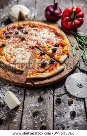 Pizza with cheese ham peppers and olives on the board - stock photo