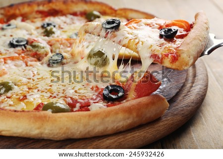 Pizza with cheese on board and wooden table background - stock photo