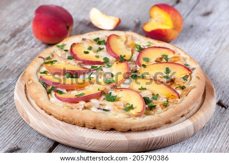 Pizza with chicken and peaches on a wooden board