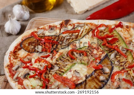Pizza with chicken, zucchini, eggplant and mushrooms on wooden rustic table - stock photo