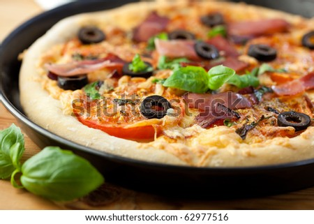 Pizza with ham and tomatoes - stock photo