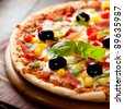 Pizza with ham, pepper and olives - stock photo