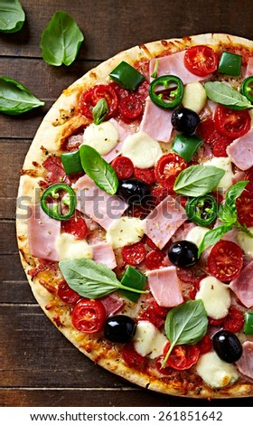 Pizza with ham, pepperoni, hot peppers and mozzarella  - stock photo