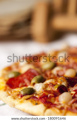 Pizza with ham, salami, olive, bacon, onion