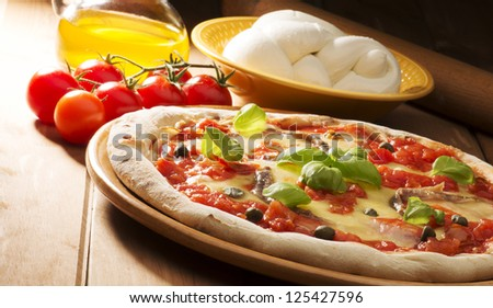 pizza with ingredients on wooden table - stock photo