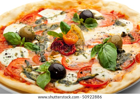 Pizza with Mozzarella Cheese and Fresh Tomato and Pesto Sauce. Garnished with Dried Tomato, Green and Black Olives and Basil Leaves - stock photo
