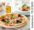 Pizza with Mozzarella Cheese, Fresh Tomato and Pesto Sauce. Served at Restaurant Table - stock photo