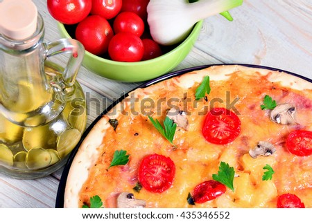 Pizza with mushrooms and ingredients close-up on a white wooden table