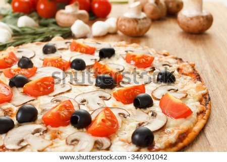Pizza with mushrooms, olives and tomatoes. Basil, rosemary and fresh vegetables. Freshly homemade  - stock photo