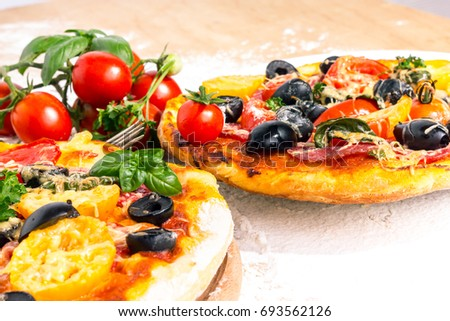 Pizza with olives and tomatoes on a table in flour