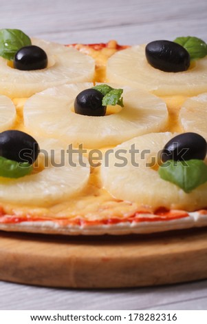 Pizza with pineapple rings, olives and basil on the table. close-up