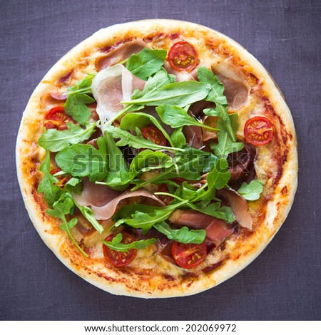 Pizza with prosciutto and arugula (salad rocket) top view - stock photo