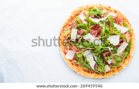 Pizza with prosciutto (parma ham), arugula (salad rocket) and parmesan on white background top view. Italian cuisine. Space for text. - stock photo